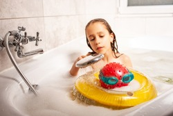 Funny little unidentified girl showering a head made of a ball and swimming goggles from the shower while bathing in the bathroom at home. Concept of childish fantasy