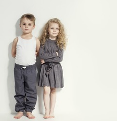 Funny lovely children. Fashionable little boy and girl in grey and white clothes and  barefoot. stylish kids in casual clothes with  different emotions. fashion children