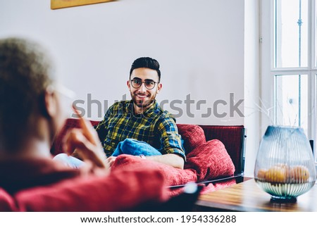 Funny male in classic eyewear have positive conversation with blurred friend discussing fellowship in comfortable flat, carefree hipster guy enjoying daytime for talking with personal psychologist