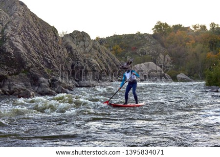 Funny man dressed as an elk (moose) is paddling on a SUP board on fast mountain whitewater river among the rapids at dusk at dusk. Costume water show. Stand up paddle boarding - active recreation. #1395834071