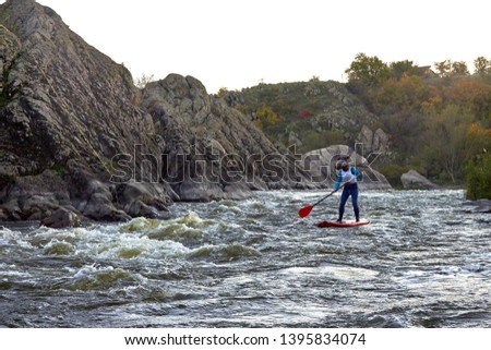 Funny man dressed as an elk (moose) is paddling on a SUP board on fast mountain whitewater river among the rapids at dusk at dusk. Costume water show. Stand up paddle boarding - active recreation. #1395834074