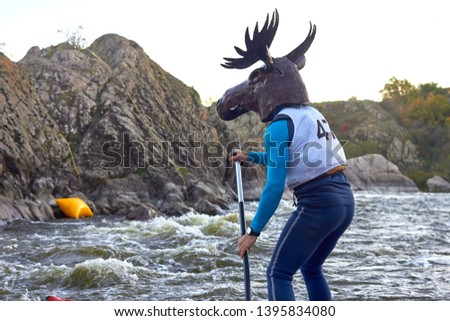 Funny man dressed as an elk (moose) is paddling on a SUP board on fast mountain whitewater river among the rapids at dusk at dusk. Costume water show. Stand up paddle boarding - active recreation. #1395834080