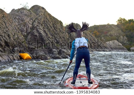 Funny man dressed as an elk (moose) is paddling on a SUP board on fast mountain whitewater river among the rapids at dusk at dusk. Costume water show. Stand up paddle boarding - active recreation. #1395834083