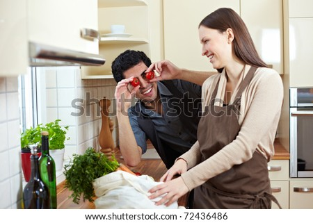 Funny man holding tomatoes in front of his eyes in kitchen