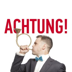 Funny man in blue bow tie blowing into the trumpet with title 'attention' german language