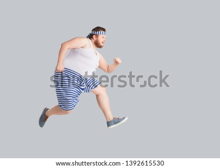 Funny man in striped shorts runs on a gray background. #1392615530