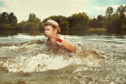 Funny man in stylish retro swimsuit and straw hat swimming in river