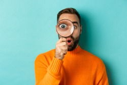 Funny man looking through magnifying glass, searching or investigating something, standing in orange sweater against turquoise background