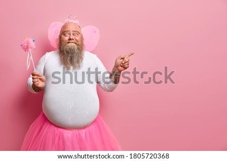 Funny man wears fairy costume, invites you on holiday or costume party, indicates right at blank space, holds magic wand, poses against rosy wall. Dad entertains children during birthday celebration