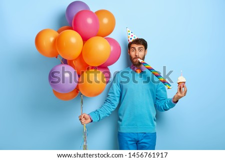 Funny man with bristle, wears party hat, blows horn, holds sweet muffin with burning candle, holds bunch of multicolored balloons, going to have birthday celebration, isolated on blue background #1456761917