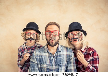 Funny man, woman and kid with fake mustache. Happy family playing in home
