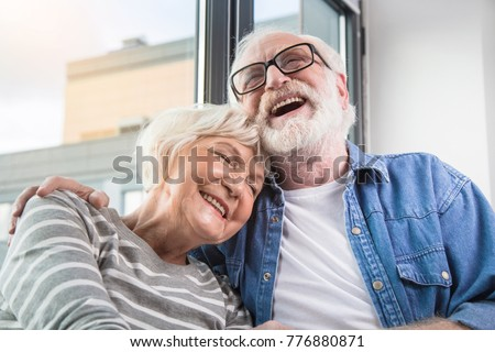 Funny memories. Waist up portrait of old happy man and woman remembering sweet moments while smiling with closed eyes