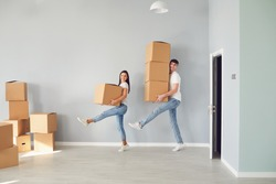 Funny middle-aged couple with cardboard boxes smiling in a new apartment.