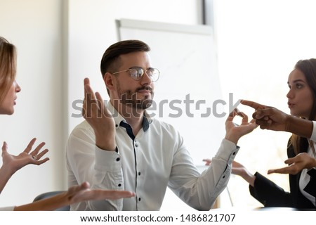 Funny mindful business man meditate with patience eyes closed at meeting ignore angry annoying colleagues clients argue at work do yoga exercise keep calm reduce pressure feel stress relief in office