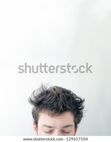"""Funny morning look of a young adult men with on a white (greenish/blueish) background - not """"isolated"""". This is also the Hangover or just """"a bad night"""" look. You can see a bit of fatigue."""