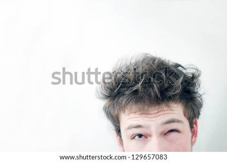 "Funny morning look of a young adult men with on a white (greenish/blueish) background - not ""isolated&quot ;. This is also the Hangover or just ""a bad night"" look. You can see a bit of fatigue. - stock photo"