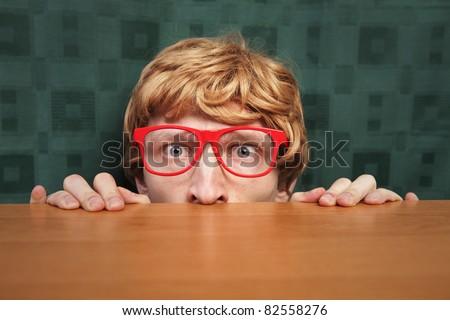 Funny nerd hiding behind a desk