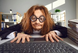 Funny nerd in round thick lens glasses sitting at desk and using laptop. Crazy looking office worker or computer geek typing on keyboard, searching for information on the Internet or doing accounts