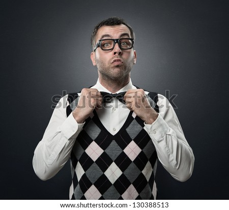 Funny nerd preparing to go out for a date isolated over dark gray textured background