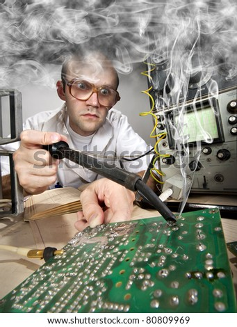 Funny nerd scientist soldering at vintage technological laboratory