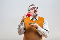 Funny nerdy man enjoys drinking coffee.Nerdy man drinking coffee