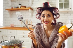 Funny newbie housewife having trouble in kitchen. Woman in bathrobe and hair curlers shrugging shoulders not knowing how to cook soup, feeling bad, stressed, confused, awkward, embarrassed, helpless