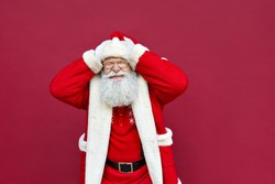 Funny old bearded Santa Claus wearing costume holding head in hands feeling headache or stress forgot about Christmas, desperate about mistake, suffering from memory loss isolated on red background.
