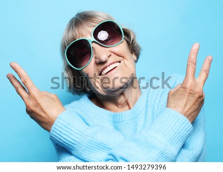 Funny old lady wearing blue sweater, hat and sunglasses showing victory sign. #1493279396