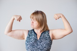 funny older person happy thick fat woman female showing muscles indoors self isolation quarantine