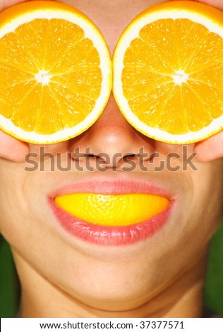 Funny orange and health concept - you just can't have too many oranges!  Funny picture of woman with orange.