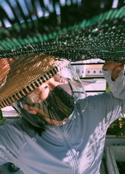 Funny outdoor concept for prevent corona virus, Vietnamese woman wear black face mask and bamboo hat with windshield, close up eyes looking up to sky in sunny morning make amazing shadow and shade