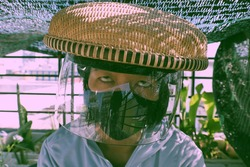 Funny outdoor concept for prevent corona virus, Vietnamese woman wear black face mask and bamboo hat with windshield, close up face with goggle eyes in sunny morning make amazing shadow and shade
