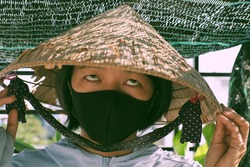 Funny outdoor concept for prevent corona virus, Vietnamese woman wear black face mask and old conical hat, close up face with goggle eyes in sunny morning make amazing shadow and shade