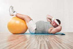 Funny overweight man working out on the floor