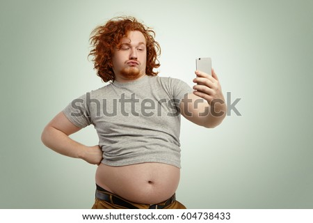 Funny overweight plump man with duck lips wearing undersize t-shirt with belly hanging out of pants, keeping hand on waist, posing for selfie, holding cell phone, trying to seem attractive and sexy #604738433