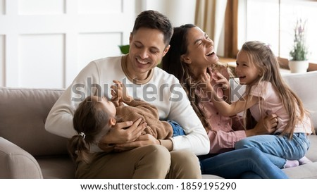 Funny parents play with two daughters resting on couch in light cozy living room. Family enjoy playtime together at home, tickling each other laughing feels happy. Having fun at home with kids concept