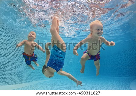 Funny photo of active babies swim and dive with fun - jump deep down underwater with splashes in swimming pool. Family lifestyle and summer children water sports activity and lessons with parents.
