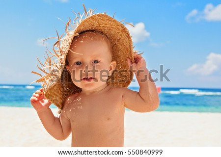 Funny photo of happy baby boy on beach with straw hat and dirty face covered with sand. Family travel, healthy lifestyle, recreation, water outdoor activity on summer beach vacation with children.