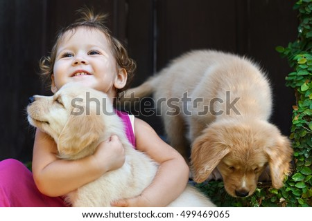 Funny photo of happy baby girl hugging and playing with beautiful golden labrador retriever puppy. Positive emotions of children fun games with home pet on summer vacation.