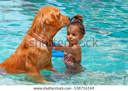 Stock Photo Funny photo of little baby swimming in outdoor pool, playing with retriever puppy. Children water sports activity and swimming lessons, training dogs, fun games with family pet on summer vacation.