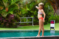 Funny photo of little child stand by outdoor swimming pool. Family lifestyle, kids water sport activity on summer holiday
