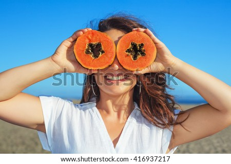 Shutterstock Funny photo of positive adult woman with smiling face holding in hands ripe fruit - orange papaya slices. Healthful food, low calories breakfast on sea beach Healthy lifestyle on summer family holiday