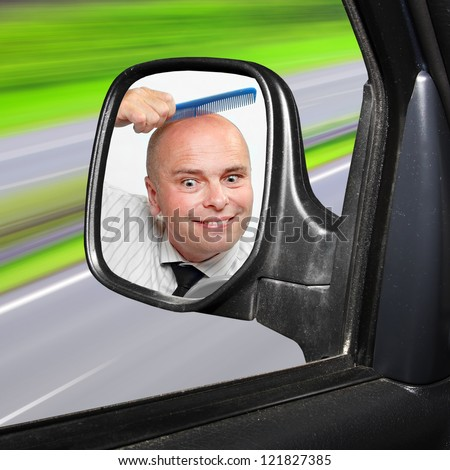 Funny picture of a careless driver combing his hairless head.  Highway traffic safety concept.