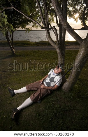 Funny picture of a golf player taking a nap under trees. Holding a golf ball in his hand.