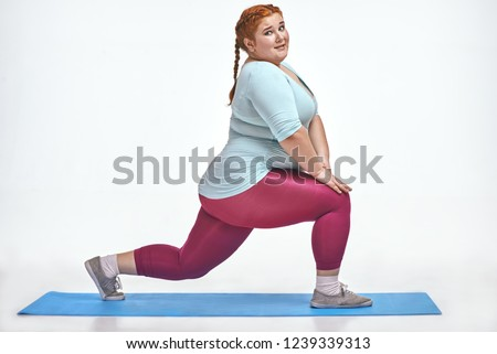 Funny picture of amusing, red haired, chubby woman on white background. Woman trains on the mat.