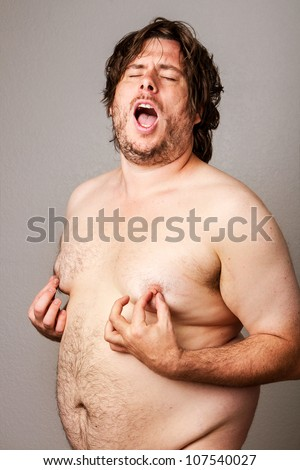 Funny picture of an overweight man pinching his own nipples while standing their nude