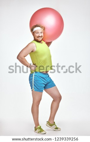 Funny picture of red haired, bearded, plump man on white background. Man wearing sportswear. Man holding fitness ball