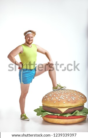 Funny picture of red haired, bearded, plump man on white background. Man wearing sportswear. Man put his leg to a huge sandwich