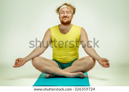 Funny picture of red haired, bearded, plump man on white background. Man wearing sportswear. Man sitting on the mat, he is meditating