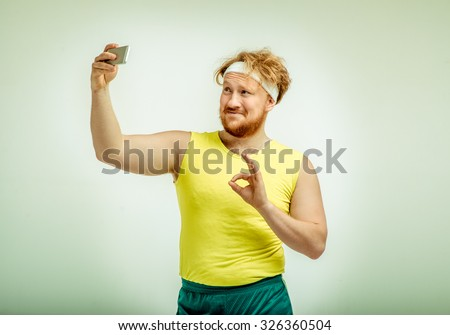 Funny picture of red haired, bearded, plump man on white background. Man wearing sportswear. Man smiling and taking a selfie